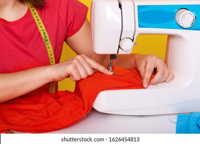 Image of seamstress being at her workplace, working hard, making little stitches along bright red fabric with help of electronic sewing machine located on desk surface. People and working concept.