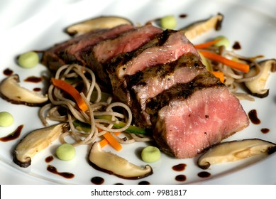 Image of seared sliced beef with vegetable garnish