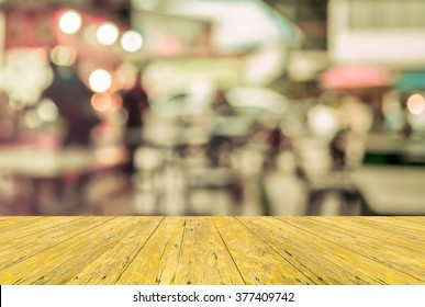 image of selective focus on surface of wood table and blur people at food stall with bokeh for background usage . (vintage tone)