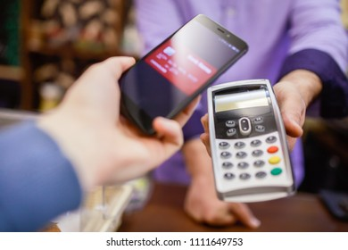 Image of seller man with terminal and buyer with smartphone