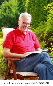 Image of senior man sitting in garden at home and reading book.