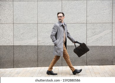 Image of serious adult businessman in eyeglasses walking with bag near concrete wall outdoors
