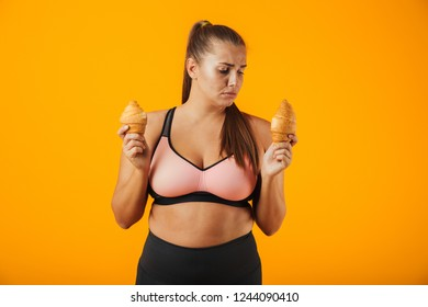 Image of serious chubby woman in tracksuit holding two croissants in both hands isolated over yellow background