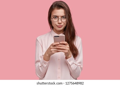 Image of serious girlfriend with displeased facial expression, presses lips, carries modern cell phone, communicates in social networks, dressed in fashionable shirt, models over pink background