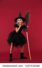 Image of serious little girl witch in carnival halloween costume isolated over red wall background with broom showing silence gesure.