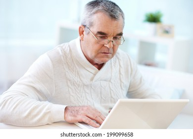 Image of serious pensioner using laptop at home