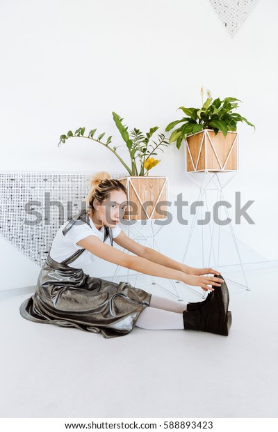 Image of serious young asian lady posing over white wall with plants. Looking at camera.