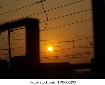 The image of setting sun as seen through verandah railing and electric wires.