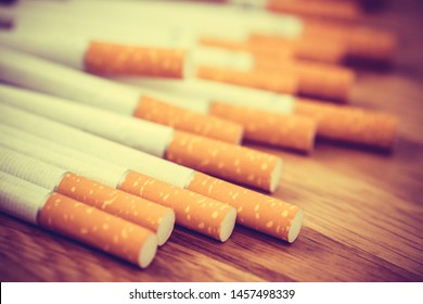 image of several commercially made cigarettes. pile cigarette on wooden. or Non smoking campaign concept, tobacco. filter vintage retro.