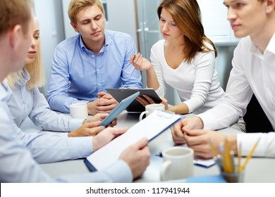 Image of several employees discussing new ideas in groups at meeting