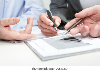 Image of several hands over business charts