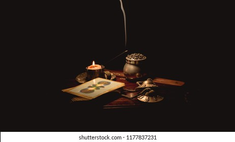 Image of several objects used in Buddhist alternative therapies: tingsha bells, candles and incense sticks with tarot cards. Image on black background and wooden table.