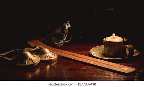 Image of several objects used in Buddhist alternative therapies: tingsha bells, candles and incense sticks. Image on black background and wooden table.