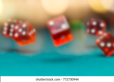 Image of several red dice falling on green table in casino