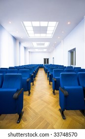 Image of several rows of dark blue armchairs in conference hall