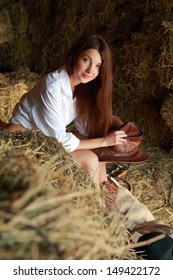 Image of sexy young woman with long dark hair wearing a cowboy hat and denim shorts in the hayloft
