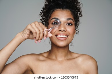 Image of shirtless african american woman using eyelashes curler and smiling isolated over grey wall