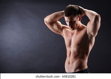 Image of shirtless man in jeans looking downwards with his hands on top of head