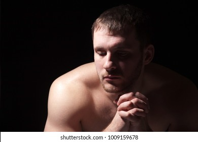 Image of shirtless man keeping his hands by face while thinking