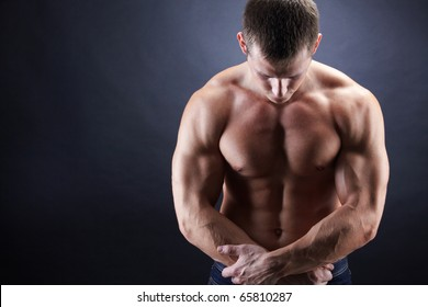 Image of shirtless man looking downwards with his arms crossed by stomach