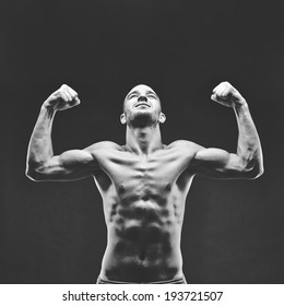 Image of shirtless man looking upwards with raised arms in front of camera