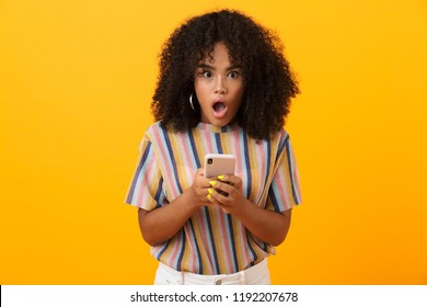 Image of shocked emotional african woman posing isolated over yellow background using mobile phone.