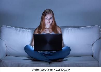 Image of shocked girl using facebook at night