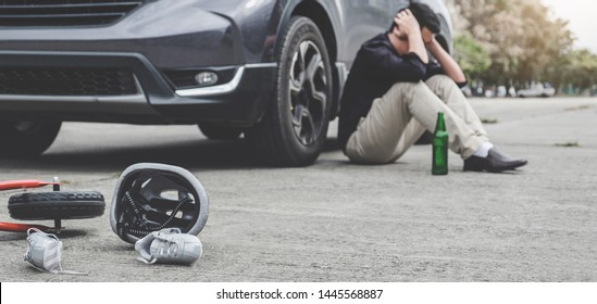 Image of shocked and scared driver after accident involved Kid's bike and helmet lying on the road on pedestrian crossing after accident collision with drunk car driver.