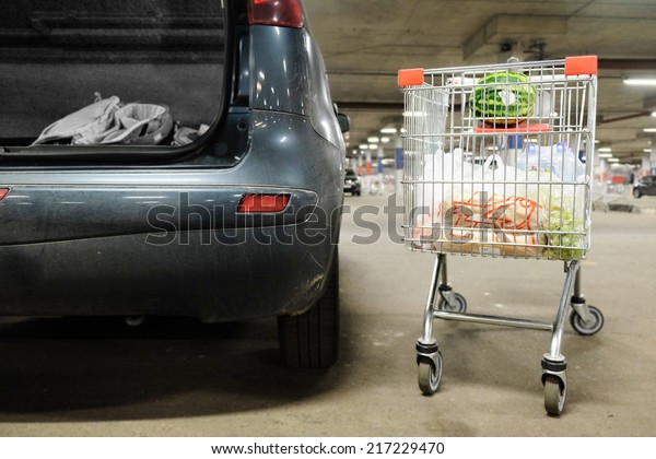 the image of a shopping tolley near the car