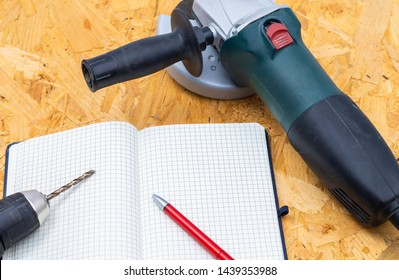 The image shows an angle grinder with a driller and notebook on a wooden table