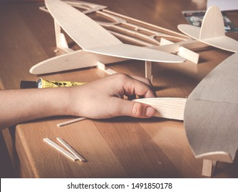 image shows a balsa wood aircraft model and kids hand holding a second wooden flight model