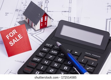 The image shows a calculator and a sold house