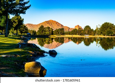 The image shows a calm lake in  the early morning with reflections of Camelback Mountain and trees visible in the distance
