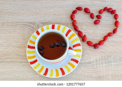 image shows a cup of tea placed on a wooden surface and seeds of Rosa canina plant making a heart.Healthy way of living concept.