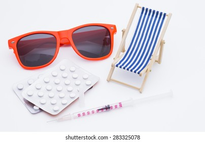 Image shows a deck chair, sunglasses, pills and a injection