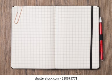 Image shows an empty notebook opened on wood-ground