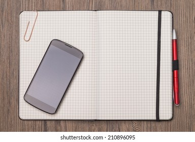 Image shows an empty opened notebook with mobile on wood-ground