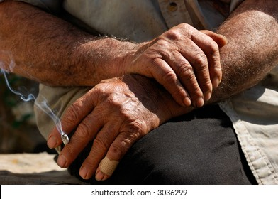 Image shows the hands of a hard working man as he enjoys his cigarette