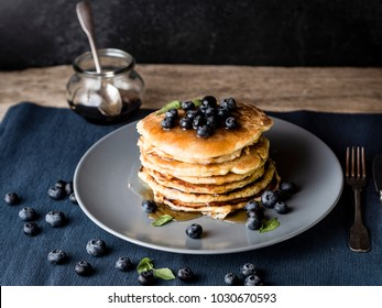 image shows a homemade fluffy pancake with blueberry on the top; situation is decorated with rustiv wooden table, placemat, silver cutlery, honey glass