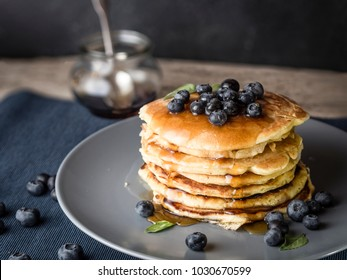 image shows how to make the best blueberry pancake stacks; rustic wooden table is decorated with rustic placemat and honey glass at the  background