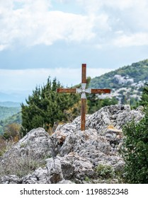 Image shows an iron cross fastened to a rock that lies in a mountain.