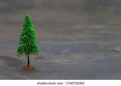 Das Bild zeigt einen Modellbaum auf grauem Schiefer
