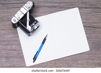 Image shows a notepad with pen and camera on a wooden table