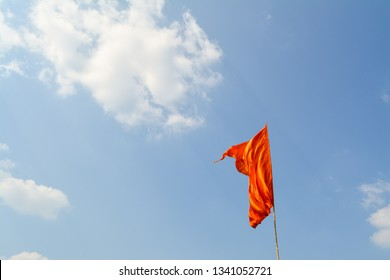 The image shows a Orange flag that belongs to Marathi/ Hindu caste/ religion, with a blue sky in the background