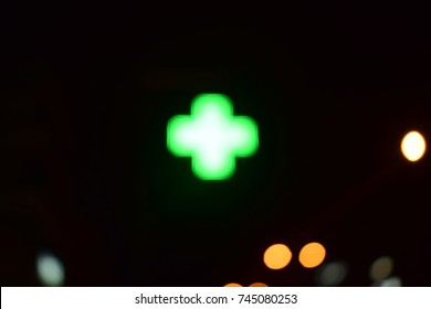 Image shows an out of focus-blurred pharmacy's cross. Photo is suitable for healthcare concept.