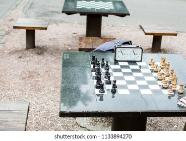 Image shows an outdoor chess table with clock ready for battle.