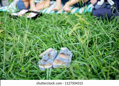Image shows a pair of kid's sandals on the grass while  the mother and son are sitting on a mat at the background.