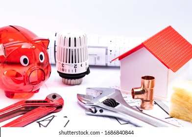 Image shows a red piggy bank with a model house, floorplan and various tools, isolated on a white background