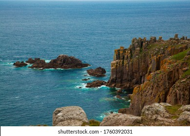 Image shows rugged Cornish coast of Britain with rock formations, cliffs and islets that are part of an archipelago. A rough but scenic coastline.