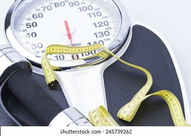 Image shows a scale, measuring tape and a dumbell